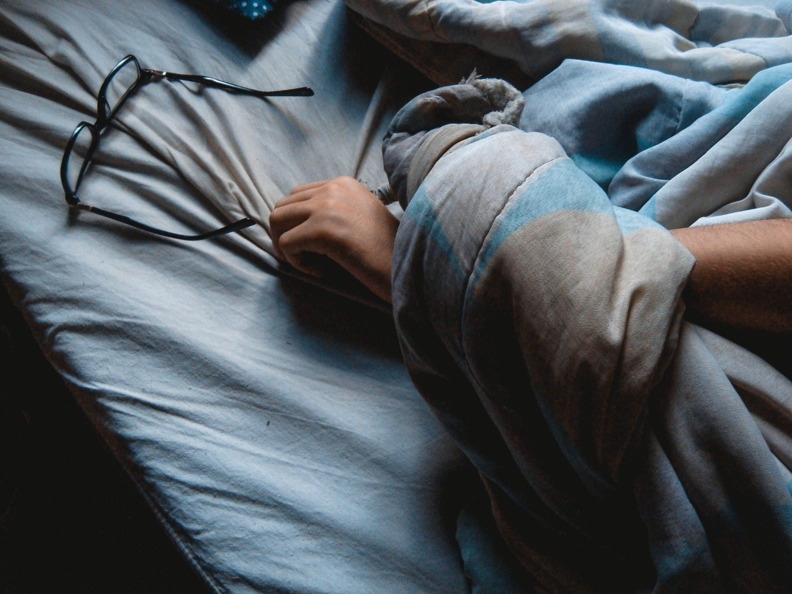 Image d'une personne dormant dans son lit pour symboliser le sommeil